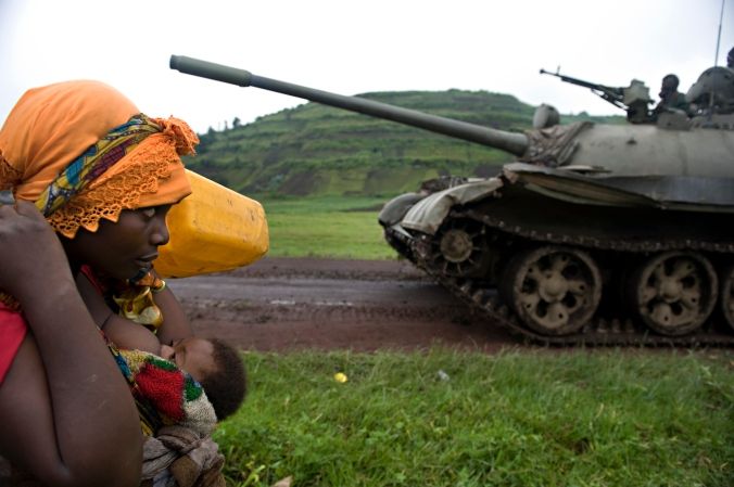 KIBUMBA, DEMOCRATIC REPUBLIC OF CONGO - OCTOBER 27, 2008: A Congolese woman carrying her child and belongings passes a Congolese army tank near Kibumba, about 35 kilometers (21.7 miles) north of the provincial capital Goma. (Photo by Walter Astrada for Oleiros Revela Grant)